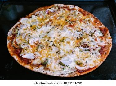 pizza mediterránea en la vieja bandeja de horno
