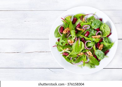 Mediterranean red beans salad with mix of lettuce leaves and walnuts on a white dish on a wood table with blank space left, italian style, close-up