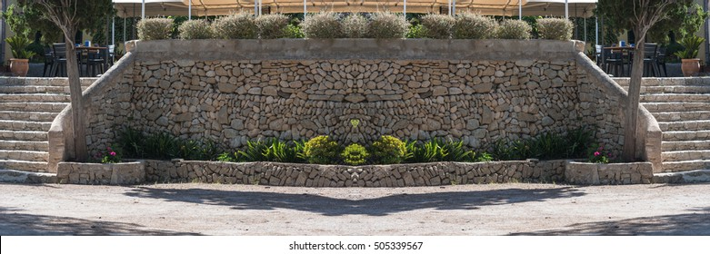 Mediterranean retaining wall of traditional natural stone for a terrace of a restaurant.