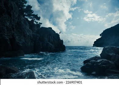 Mediterranean rocky shores and landscape - Odysseus cave on island Mljet near Dubrovnik, tourist attraction, Croatia. Young man jumping from the cliff in distance. Cliff jumping recreation on seaside