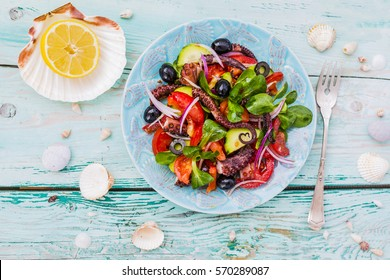 Mediterranean salad with grilled octopus on wooden background.