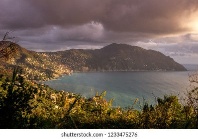 Mediterranean Sea: Beautiful aerial view of Camogli and Ligurian coast at sunset with stormy sky and dramatic dark clouds. Punta Chiappa and Portofino promontory, Liguria Regional Park