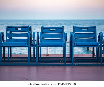 Mediterranean Sea and famous blue chais on Promenade des Anglais at sunset in Nice, Cote d'Azur, France