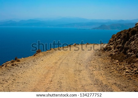 Mediterranean sea and gravel dangerous road, which leads to Gramvousa beach on island of Crete in Greece