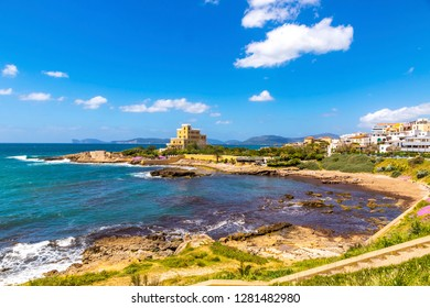 Mediterranean seacoast in Alghero city, Sardinia, Italy. Spring flowers and trees on foreground, colourful buildings of Alghero old city center on background