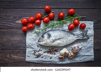 Mediterranean seafood concept. Raw dorado fish with garlic, tomatoes and rosemary on wooden table. Fresh organic sea bream or dorada fish. Top view, copy space
