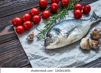 Mediterranean seafood concept. Raw dorado fish with garlic, tomatoes and rosemary on old wooden table. Fresh organic sea bream or dorada fish. Top view, copy space