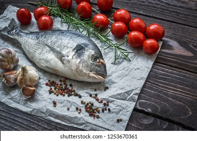 Mediterranean seafood concept. Raw dorado fish with garlic, tomatoes, pepper and rosemary on old wooden table. Fresh organic sea bream or dorada fish. Top view, copy space
