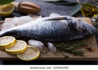 Mediterranean seafood concept. Raw dorado fish with olive oil, lemon, rosemary on stone table. Fresh organic sea bream or dorada fish. Top view