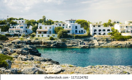 Mediterranean seascape with some white villas on the coast, rocks and blue sky with white clouds. Mallorca (Cala d'Or).