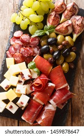 Mediterranean snack of cheese platter, prosciutto ham, grapes, figs, sausages and olives close-up. Vertical top view from above