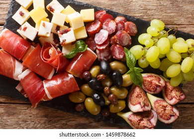 Mediterranean snack of cheese platter, prosciutto ham, grapes, figs, sausages and olives close-up. Horizontal top view from above
