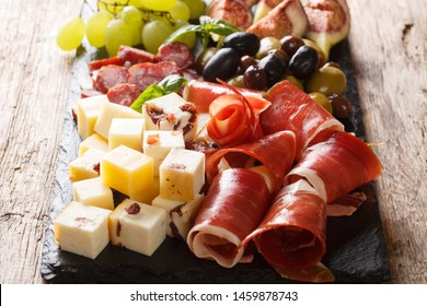 Mediterranean snack of cheese platter, prosciutto ham, grapes, figs, sausages and olives close-up. horizontal