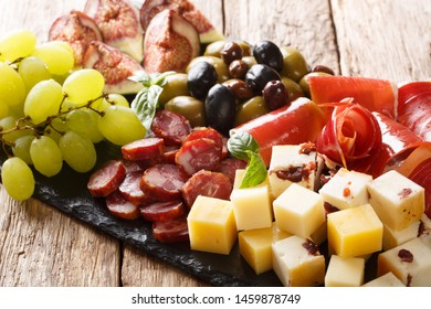 Mediterranean snack dish of cheese, prosciutto ham, grapes, figs, sausages and olives close-up on a wooden table. horizontal