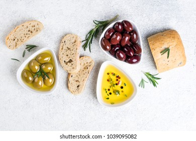 Mediterranean snacks. Ciabatta bread, olives, oil, herbs and spices on white background. Top view