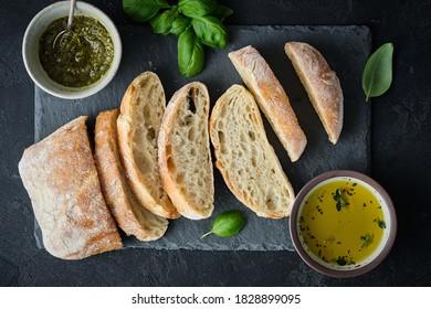 Snack méditerranéen. Olives, huile, herbes et pain ciabatta tranché. Vue de dessus.