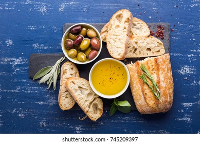 Mediterranean snacks set. Olives, oil, herbs and sliced ciabatta bread on black slate stone board over painted dark blue background, top view