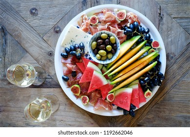Mediterranean snacks for wine. Olives, prosciutto, jamon, melon, watermelon, grapes, cheese brie, fig. Top view, vintage wooden table
