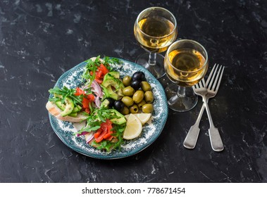 Mediterranean style antipasto and wine. Smoked salmon, avocado, arugula bruschetta, olives and two glasses of white wine on dark background