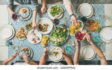 Mediterranean style dinner. Flat-lay of table with salads, starters, pastries over blue table cloth with hands holding drinks, sharing food, top view. Holiday gathering and vegetarian party concept
