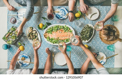 Mediterranean style dinner. Flat-lay of table with cooked salmon, starters, bread over blue table cloth with hands holding drinks, sharing food, top view. Holiday party concept