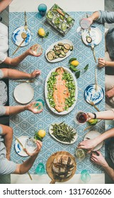 Mediterranean style dinner. Flat-lay of table with cooked salmon, starters, bread, lemonade over blue table cloth with hands holding drinks, top view, vertical composition. Holiday party concept