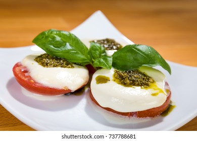 Mediterranean style food: Grilled tomato with slightly melted mozzarella cheese and basil pesto as well as basil leaves.