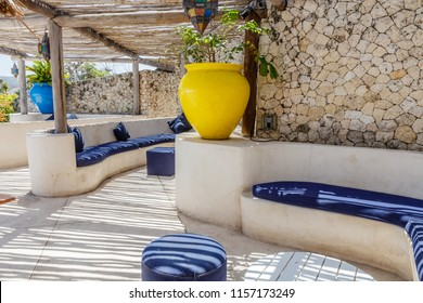 Mediterranean style interior in yellow, white and blue colors with rustic twig ceiling providing striped shadow over sofas and cushions, wooden floors, stone walls, ceramic pots.