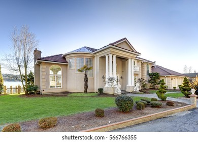 Mediterranean style luxury waterfront home features Low-pitched tile roof, stucco walls, columned porch and arch motifs. Well-manicured landscape design creates perfect curb appeal. Northwest, USA