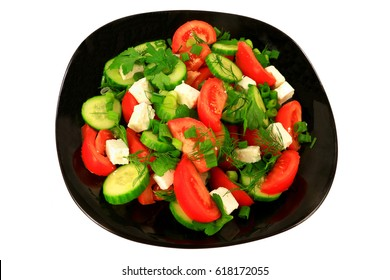 Mediterranean style salad from tomato wedges, sliced seedlesscucumber, Feta cheese seasoned with green onion, parsley, and dillserved on a black porcelain dish over white background