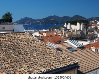 Mediterranean style shingle tiles are see on rooftops in Cannes, France, Europe with Old Cannes in distance of harbor