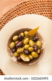 Mediterranean tapas appetizers serving bowl with green and black olives, dried herbs and bay leaf leaves. Selective focus on surface of olives. Vertical flat lay still life image with copy space.