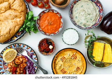 Mediterranean traditional meze: hummus, babaganoush, harissa tzatziki on white background, top view