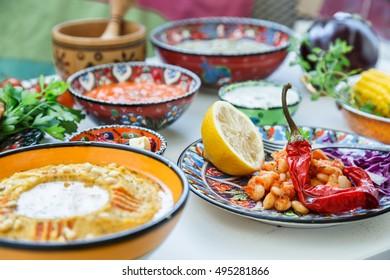 Mediterranean traditional meze: hummus, babaganoush, harissa tzatziki on white background