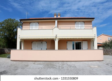 Mediterranean villa divided with four apartments and large front balcones surrounded with stone tiles and trees with houses on cloudy blue sky background