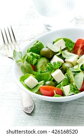 Mediterranean-style Salad with feta cheese, organic green olives, cherry tomatoes, cucumber, fresh basil and parsley.  Greek salad. Healthy snack. Concept for a tasty and healthy meal.