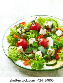 Mediterranean-style Salad with Feta Cheese, Red Pepper, Organic Green Olives, Cucumber, Lettuce, Spices and Fresh Basil. Summer Salad. Concept for a tasty and healthy meal.