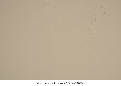 Medium beige concrete wall with randomly plastered structures and light soiling in industrial design. Pastel colored stone wall as background and design element for art. Bright dark gradients.