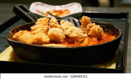 Medium close-up detail shot of korean food bimbimbap and topokki in the black hot plate with korean sauce gochujang and  kimchi