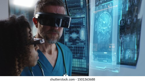 Medium close-up of a doctor discussing brain scan results while wearing VR headsets