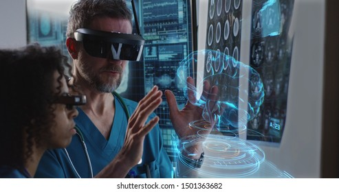 Medium close-up of a male and a female doctor examining 3D brain hologram while wearing VR headsets