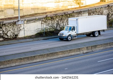 Medium duty rig compact size white industrial semi truck for local deliveries transporting commercial cargo for timely delivery in dry van box trailer running on the divided wide highway road