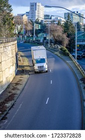 Medium duty rig compact size white industrial semi truck transporting commercial cargo for timely delivery in dry van box trailer running downhill road from the city street to highway entrance