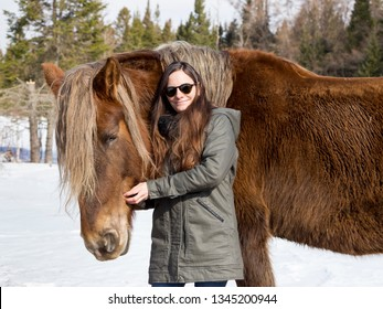 Medium frontal shot of smiling long-haired brunette young woman in warm clothes and sunglasses petting sturdy tall rust coloured horse against winter countryside landscape