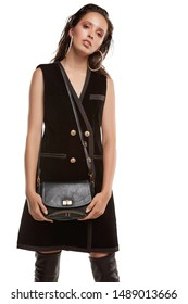 Medium full shot of a young chestnut European lady with a crossbody bag and dressed in a brown buttoned dress and dark over-the-knee boots. The bag is made of black leather with a golden fastener