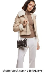 Medium full shot of a young chestnut European lady with a shoulder bag and dressed in a brown buttoned dress and dark over-the-knee boots. The transparent crossbody bag with leather surround,