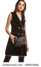 Medium full shot of a young chestnut European lady with a crossbody bag and dressed in a brown buttoned dress and dark over-the-knee boots. The bag is made of black leather with a fretted pattern,