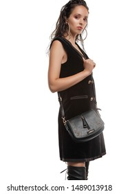 Medium full shot of a young chestnut European lady with a crossbody bag and dressed in a brown buttoned dress and dark over-the-knee boots. The bag is made of black leather with a pattern of glossy