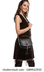 Medium full shot of a young chestnut European lady with a crossbody bag and dressed in a brown buttoned dress and dark over-the-knee boots. The bag is made of black leather with fringed wisps,
