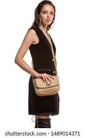 Medium full shot of a young chestnut European lady with a crossbody bag and dressed in a brown buttoned dress and dark over-the-knee boots. The bag is made of light beige leather